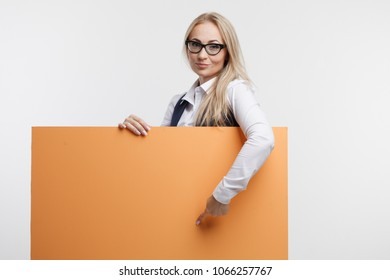 Smiling business woman showing thumb up holds white sign board, advertising banner. Isolated studio portrait