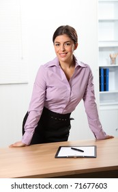 Smiling business woman standing behind office desk