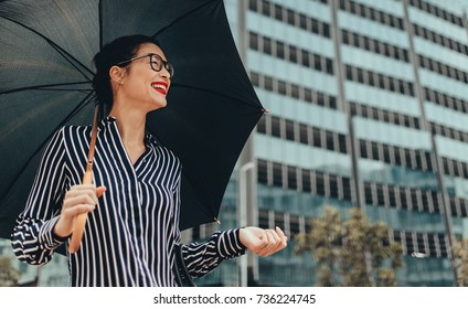 Smiling business woman walking on city street with umbrella.  Happy female business professional with umbrella walking down city street.