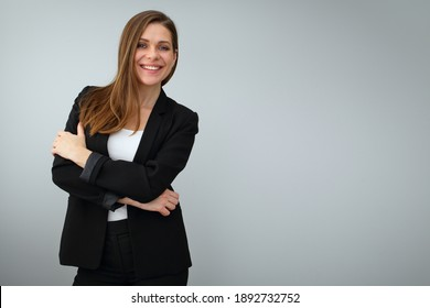 Smiling business woman wearing black suit standing with crossed arms. Isolated portrait on gray back.