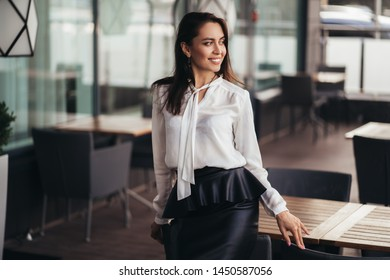 Smiling business woman in white shirt and black skirt poses in cafe, beautiful girl rests during her break