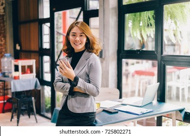 Smiling Business woman working in office with documents,Happy Asian businesswoman using phone sitting on chair at modern home studio.Concept of young people working mobile devices,contact to costumer
