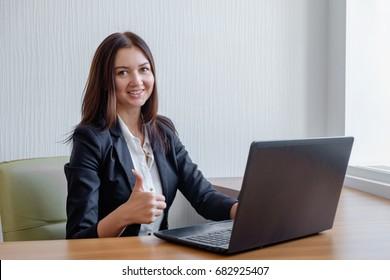 smiling business woman working on laptop and shoving thumbs up