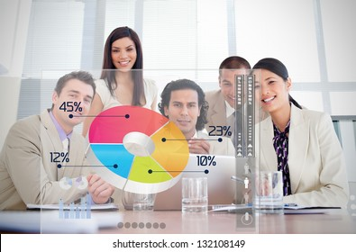 Smiling business workers looking at colorful pie chart interface in a meeting