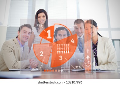 Smiling business workers looking at orange pie chart interface in a meeting
