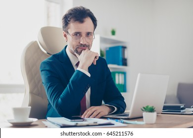 Smiling businessman banker is sitting at his workplace and looking in camera. He is wearing formalwear, glasses