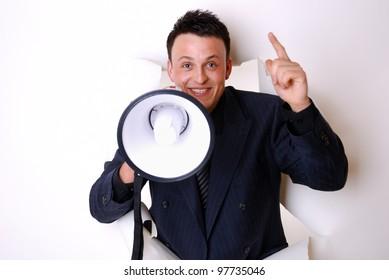 smiling businessman break through a paper wall