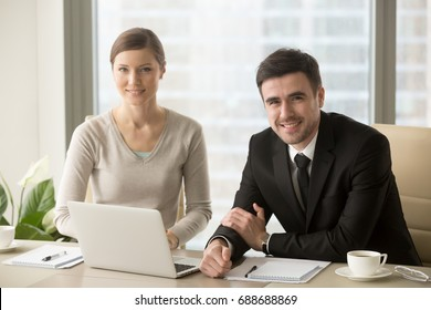 Smiling businessman and businesswoman looking at camera, confident successful boss and professional assistant posing at workplace sit in front of laptop, talented motivated business team portrait