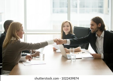 Smiling businessman and businesswoman shaking hands over conference table, company executive welcoming new business partner at diverse team meeting, gender equality business handshake concept