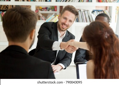 Smiling businessman and businesswoman shaking hands sitting at meeting table, new partners greeting making first impression starting group negotiations teamwork, satisfied entrepreneurs handshaking