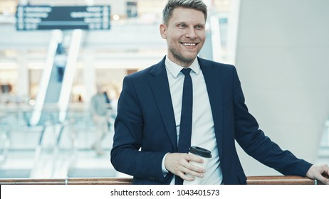 Smiling businessman with coffee in a store