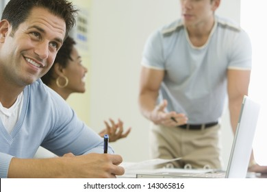 Smiling businessman with colleagues discussing in background