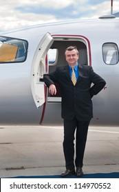 Smiling Businessman at Corporate Jet