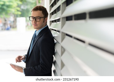 Smiling businessman with digital tablet looking at the camera