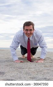 Smiling businessman doing push-ups on a beach