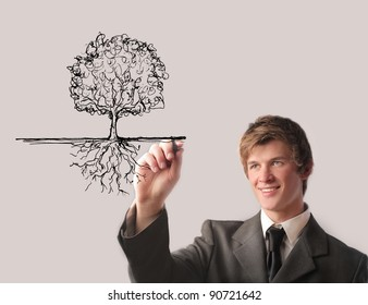 Smiling businessman drawing a tree