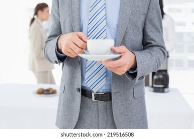 Smiling businessman with a drink at work