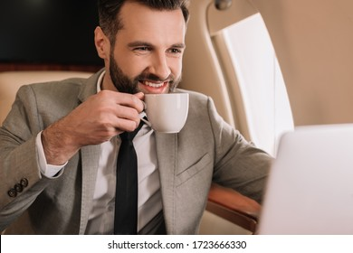 smiling businessman drinking coffee and looking at laptop in private plane