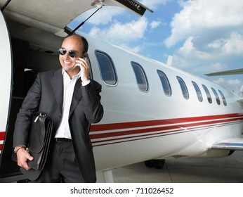 Smiling businessman exiting private jet