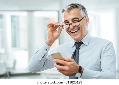 Smiling businessman with eyesight problems, he is adjusting his glasses and reading something on his mobile phone