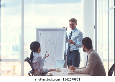 Smiling businessman with flipchart in office