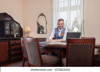 smiling businessman, formal wear, posing for a portrait. looking at camera. sitting in his apartment room, with antique furniture.
