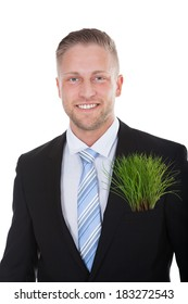 Smiling businessman with a fresh green plant in his pocket in place of a folded handkerchief in a conceptual image  isolated on white