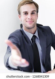 Smiling businessman giving hand for handshake, in black suit. Success in business, job and education concept shot.