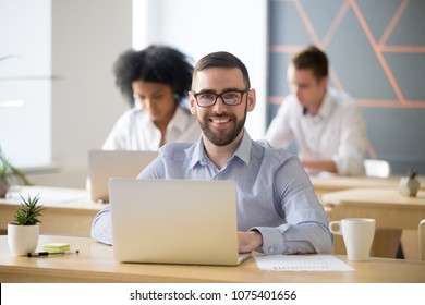 Smiling businessman in glasses sitting at desk with laptop in shared office, attractive millennial entrepreneur looking at camera in coworking, portrait of business professional posing at workplace