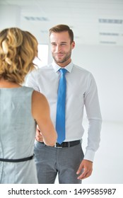 Smiling businessman greeting businesswoman with handshake in new office