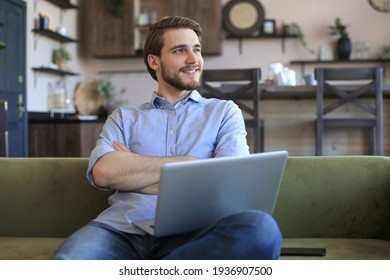 Smiling businessman greeting colleagues in video conference and negotiating distantly from home