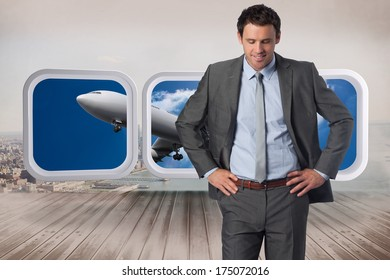 Smiling businessman with hand on hip against city scene in a room