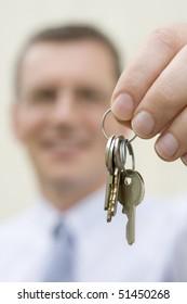 Smiling businessman handing over keys