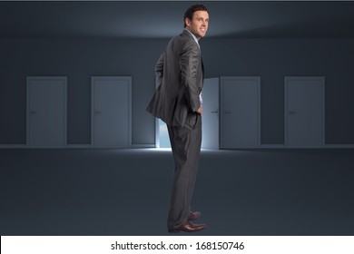 Smiling businessman with hands on hips against door opening in dark room to show sky