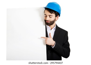 Smiling businessman with hard hat pointing on empty banner.