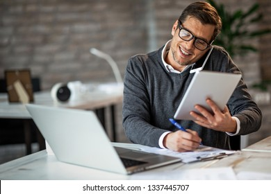 Smiling businessman having a busy day at work. He is talking on the phone while using touchpad and taking notes on the paper.