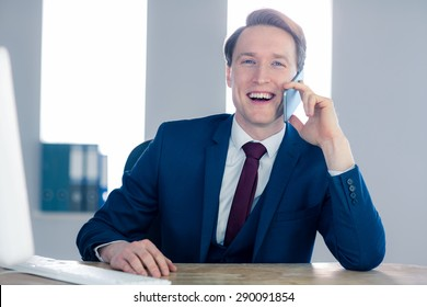Smiling businessman having a phone call in the office