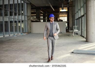 Lächelnder Geschäftsmann mit Helm auf Kopf durch die Baustelle seines Gebäudes laufen.