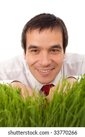 Smiling businessman hiding behind grass - isolated