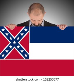 Smiling businessman holding a big card, flag of Mississippi, isolated on white