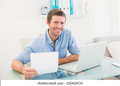 Smiling businessman holding document in his office