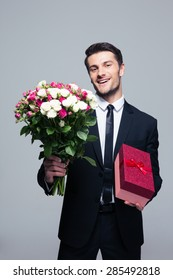 Smiling businessman holding flowers and gift box over gray background. Looking at camera