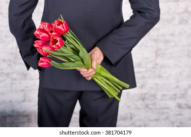 Smiling businessman holding flowers  over white background. Bouquet of flowers in his hands closeup