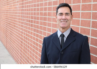 Smiling businessman isolated on urban brick wall background with copy space