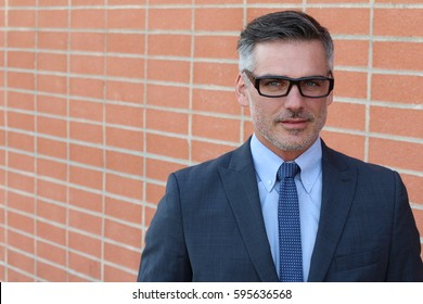 Smiling businessman isolated on urban brick wall background