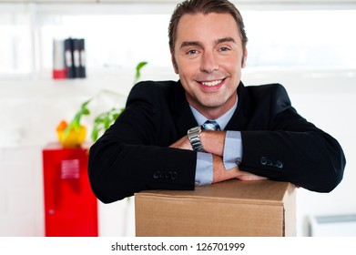 Smiling businessman keeping his arms crossed over packed carton box and smiling at camera.