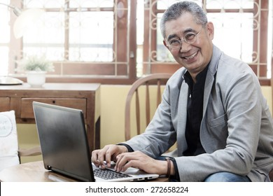 smiling businessman with laptop computer  at cafe