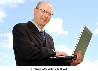 smiling businessman with laptop in front of blue sky