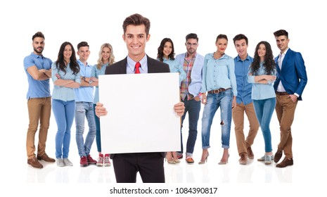 smiling businessman leader holding a blank board in front of his casual team on white background