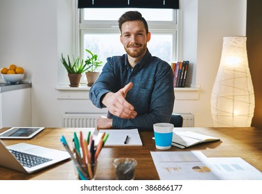 Smiling businessman leaning across his desk offering his hand in greeting, to close a deal, in partnership or congratulations